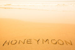 Honeymoon, text written in sand on a beach Stock Photos