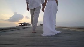 Honeymoon travel at tropics, bride in white dress walks with groom on wooden pier leading to bungalow during a luxury stock video
