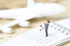 Honeymoon trip, wedding proposal, family travel tourism and vacation concept, miniature young couple standing on calendar with to. Y airplane on vintage world royalty free stock images