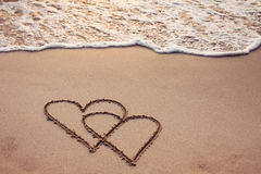 Honeymoon, Two hearts. Hearts drawn in the sand with seafoam and wave Royalty Free Stock Photo