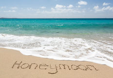 Honeymoon written in sand with sea surf Royalty Free Stock Image