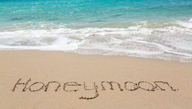Honeymoon written in sand with sea surf Stock Photos