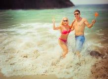 Honeymooners dobierają się odpoczywać przy ocean fala Fotografia Stock