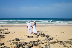 Honeymooners holding hands on a beach Royalty Free Stock Photos