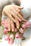 Honeymooners keep of the hands on the bouquet stock photography