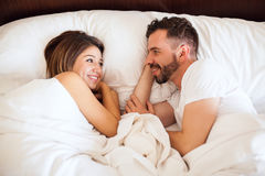 Honeymooners lying on a bed Stock Images