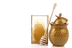 Honeypot y cuchara para la miel cerca de los peines de la miel Fotografía de archivo