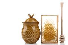 Honeypot y cuchara para la miel cerca de los peines de la miel Imagen de archivo libre de regalías