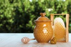 Honeypot y cuchara para la miel cerca de los peines de la miel Foto de archivo