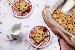 Honeysuckle crumble cake in a baking form and pieces of the cake on vintage plates stock image
