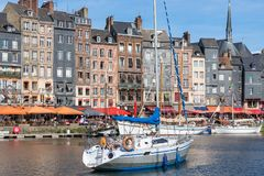 Harbor of historic city Honfleur with manoeuvring sailing ship. HONFLEUR, FRANCE - AUGUST 24, 2017: Cityscape medieval city Honfleur with manoeuvring sailing Stock Images