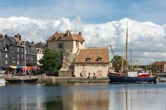 Harbor historic city Honfleur with moored sailing ships and restaurants Stock Image