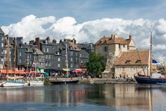 Harbor historic city Honfleur with moored sailing ships and restaurants Stock Photography