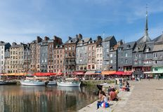 Harbor city Honfleur with moored sailing ships and relaxing people Royalty Free Stock Image