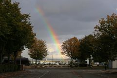 A big rainbow in the sky above the marina royalty free stock photo