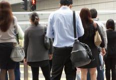 Регулярные пассажиры пригородных поездов пересекая многодельную улицу Hong Kong Стоковые Фотографии RF