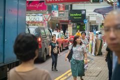 Street scene typically Asian in Hong Kong. HONG KONG, ASIA - AUGUST 2, 2017; People some partly out of frame and focus, cars, buildings and signs in busy hectic Royalty Free Stock Photo