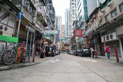 Street scene typically Asian in Hong Kong. HONG KONG, ASIA - AUGUST 2, 2017; Street scene typically Asian with high buildings along both sides and plethora neon Royalty Free Stock Photo