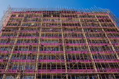 Chinese Bamboo scaffolding along the pink building stock image