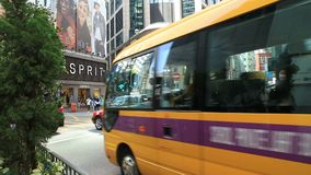 Hong Kong busy city street with traffic and people. Public transport and people crossing city street at shopping district during rush hour. Urbanscape of modern stock footage