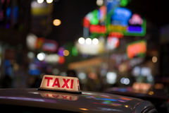 Hong Kong Cab. Taxi light reflects on roof in front of colorful background of the Causeway Bay area of Hong Kong, China royalty free stock photography