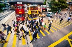 HONG KONG, CHINA - APRIL 29, 2014: De zakenlieden lopen snel langs de voetgangersoversteekplaats Onderbrekingstijd voor lunch stock afbeelding