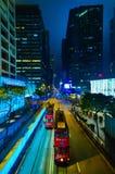 HONG KONG, CHINA - 29. APRIL 2014: Hong Kong-` s Nachtleben Zwei rote Trams überschreiten entlang die Straße mit den Shops von Ti lizenzfreie stockbilder