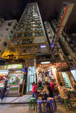 Hong Kong, China - circa September 2015: High-rise apartment building and street restaurant in Kowloon district of Hong  Kong Royalty Free Stock Photo