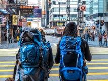 HONG KONG, CHINA - 9 de dezembro de 2016: Moça dois com a trouxa através da faixa de travessia na estrada com fundo da cidade Hon fotos de stock