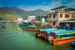 HONG KONG, CHINA - 26 DE ENERO DE 2017: Barcas en el río sucio del pueblo viejo Tai O de los pescadores con las casas rústicas, e Fotografía de archivo