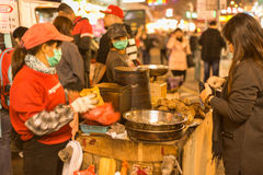Hong Kong, China, February 07,2015 -Sam Sui Po, Chestnut Seller. With Clients with clients in a cold winter night Royalty Free Stock Images