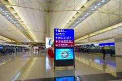 HONG KONG, CHINA - 26. JANUAR 2017: Nicht identifizierte Leute, die nahe vom informativen Zeichen innerhalb des Flughafens von Ho Lizenzfreie Stockfotografie