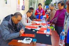 HONG KONG, CHINA - JANUARI 26, 2017: De niet geïdentificeerde mensen die wisshes over een rood document schrijven bevatten beteke Royalty-vrije Stock Foto's