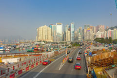 HONG KONG, CHINA - JANUARY 26, 2017: Construction site of pier, witrh some cars in a road with a city in the horizont in. Hong Kong, China royalty free stock photography