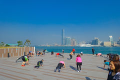 HONG KONG, CHINA - JANUARY 26, 2017: Crowd of people doing Tai Chi Exercising in the morning, with a downton of the city Royalty Free Stock Images