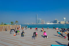 HONG KONG, CHINA - JANUARY 26, 2017: Crowd of people doing Tai Chi Exercising in the morning, with a downton of the city Stock Photography