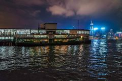 Night Star Ferry pier view in Tsim Sha Tsui in Hong Kong. Star Ferry boat on city skyline background royalty free stock photography