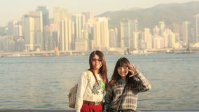 Hong Kong, China - January 1, 2016: Two young chinese tourist girls posing positively on the coast in Hong Kong, against. Two young chinese tourist girls posing Stock Image