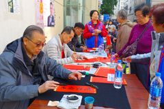 HONG KONG, CHINA - JANUARY 26, 2017: Unidentified people writting wisshes over a red paper contain meaning for Chinese. New Year wishes in Hong Kong Stock Image