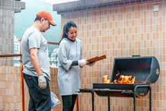 Hong Kong, China - January 17, 2016: Young couple of Caucasian man and Asian woman kindle fire on barbecue. Outdoor barbecue cooki Royalty Free Stock Photos