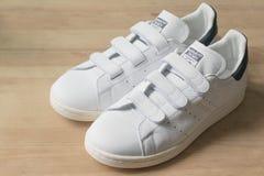 Hong Kong, China - 6. Juli 2016: Adidas-Vorlagen-Weiß und Marine Stan Smith Velcro Trainers auf einer Holzoberfläche Lizenzfreies Stockfoto