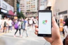 HONG KONG, CHINA - 15. MAI 2016: Eine Mannhand, die das Bildschirmfoto von Google- Mapsapp darstellend auf Fahrwerk G4 hält Googl Stockbilder