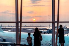 Hong Kong, China - Passagiers die op de zonsondergang letten bij de vertrekterminal stock foto