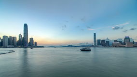 Hong Kong, China skyline panorama with skyscrapers day to night from across Victoria Harbor timelapse.