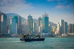 HONG KONG CHINY, STYCZEŃ, - 26, 2017: Fisher w jego łodzi z pięknego widoku ofHong Kong w horizont z, drapacze chmur i Zdjęcie Stock