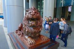 HONG KONG CHINY, STYCZEŃ, - 26, 2017: Niezidentyfikowani ludzie chodzi blisko do HSBC lwa statuy blisko kwater głównych budować H Obraz Royalty Free