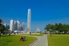 HONG KONG CHINY, STYCZEŃ, - 26, 2017: Niezidentyfikowani ludzie w parku z nowożytni budynki w finansowym gromadzkim tle, lokalizo Zdjęcie Royalty Free