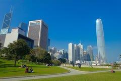 HONG KONG CHINY, STYCZEŃ, - 26, 2017: Niezidentyfikowani ludzie w parku z nowożytni budynki w finansowym okręgu Fotografia Royalty Free