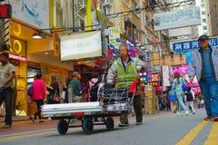 HONG KONG CHINY, STYCZEŃ, - 26, 2017: Niezidentyfikowany mężczyzna pcha up troszkę samochód przez ulicy, blisko Wiktoria parka w  Obraz Royalty Free
