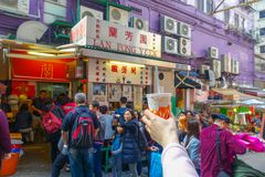 HONG KONG CHINY, STYCZEŃ, - 26, 2017: Tłum ludzie kupuje jedzenie w ulica stojaku w mieście Hong Kong Fotografia Stock
